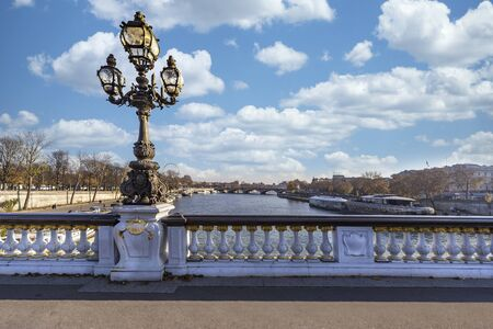 Antique lamp post on the Pont d'Alexandre III, in French under a cloudy and sunny sky, Paris, France