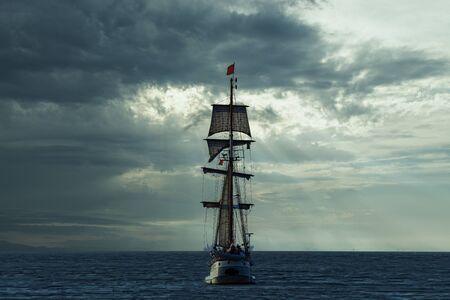 Grand voilier antique, navire quittant le port de La Haye, Scheveningen sous un coucher de soleil chaud et un ciel doré Banque d'images