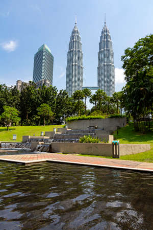 KUALA LUMPUR, 17 August 2013 - The Petronas, twin towers emerge from the KLCC garden skyline under a hash cloudless summer sky, Malaysia Editorial
