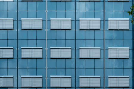 Abstract view of a build face with closed windows and blue glass wall under a hash summer sun light