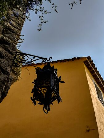 Closeup of a street light lamp on a narrow old French village with an old yellow building wall