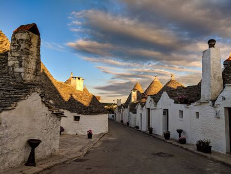 Traditional trulli houses with dry stone walls and conical roofs at sunset, in Alberobello, Puglia, Italy