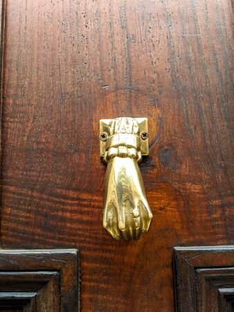 Old Golden tone Door handle in the Shape of a Hand on an ancient wooden door 스톡 콘텐츠