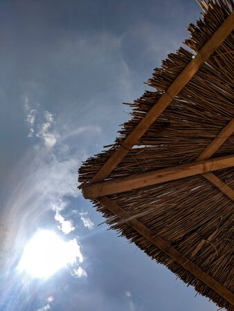 Cane beach umbrellas  Sun umbrella made of reeds on the beach against the sky 스톡 콘텐츠