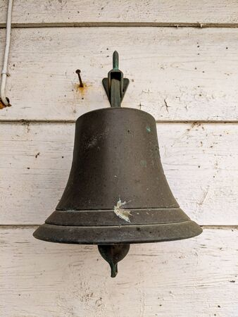 Grey large bell against a wooden old wall at the seaside 스톡 콘텐츠