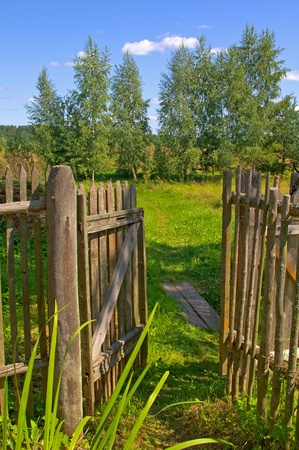 Opened wooden gate to the garden house on countryside of Russia photo