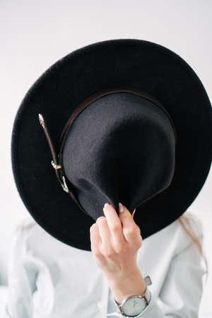 girl in a black hat on a white wall background Foto de archivo