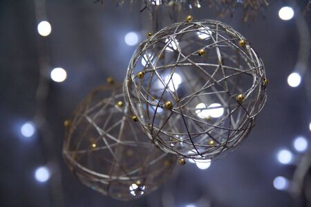 gold string: Silver Christmas globes hanging over a background of blurred lights.