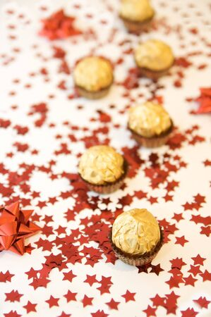 Golden wrapped chocolates on a red stars christmas background. photo