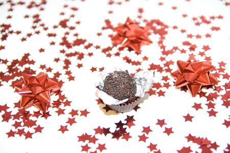 Unwrapped chocolate on a red stars christmas background. Stock Photo - 6080039