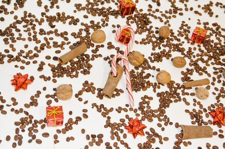 Christmas background with red candy canes, cinnamon, nuts, globes and little presents over coffee background Stock Photo - 6080043
