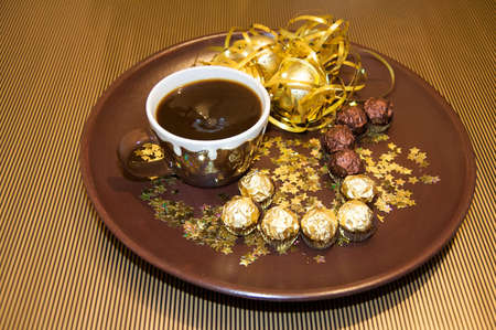 Christmas brown plate with coffee, chocolate, globes and golden stars. photo