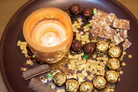 Christmas brown plate with candle, chocolate, cinnamon and golden stars. photo