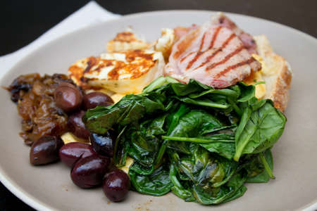 haloumi: Breakfast with toast, scrambled eggs, spinach, Haloumi cheese, fried ham, Kalamata olives and caramelized onions