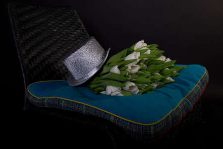 White bouquet of tulips on black chair with blue cushion Stock Photo - 11782346