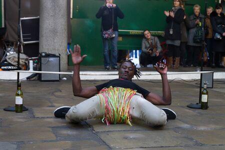 limbo: A street performer in front of Covent Garden market, London, UK, Sunday, November 13, 2011.