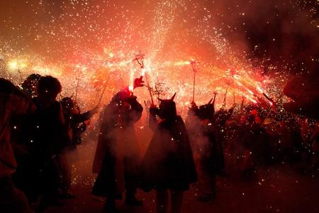 BARCELONA - AUGUST 21: Fire devils in the fire-run (Correfoc) as part of the Gracia Festival 2011 (La Festa Major de Gracia 2011) on August 21/22, 2011 in Vila de Gracia, Barcelona, Spain Stock Photo - 11828369