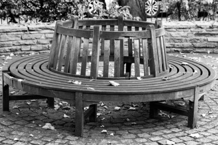 Black and white image of a round wooden bench