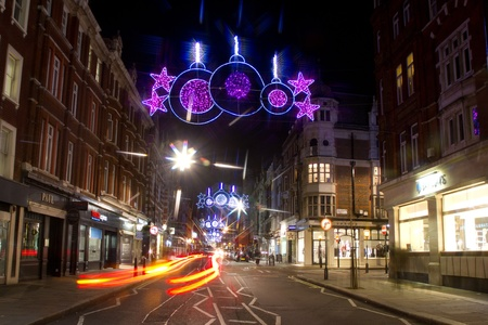 suspense: Christmas street lights and traffic by night on Marylebone Street, London, UK on 06 December 2011