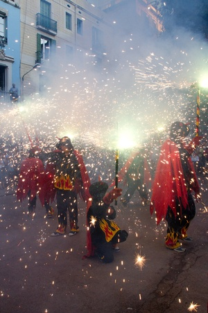 BARCELONA - AUGUST 21: Fire devils in the fire-run (Correfoc) as part of the Gracia Festival 2011 (La Festa Major de Gracia 2011) on August 2122, 2011 in Vila de Gracia, Barcelona, Spain
