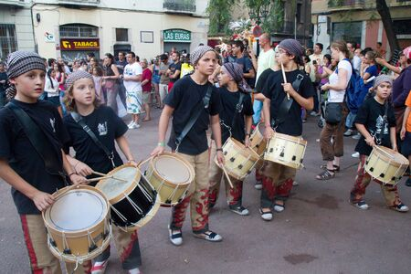 fireruns: BARCELONA - AUGUST 21: Members of the traditional drums band (gralla) in the Gracia Festival 2011 (La Festa Major de Gracia 2011) on August 21, 2011 in Vila de Gracia, Barcelona, Spain. Unidentified children