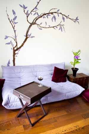 ligne: Minimalist living design with purple sofa, wooden box and blue orchid (vanda coerulea)