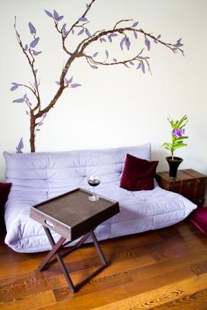 Minimalist living design with purple sofa, wooden box and blue orchid (vanda coerulea)