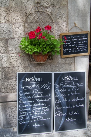A handwritten menu on a chalkboard and red flowers pot against a brick wall in front of a coffee house in Spain