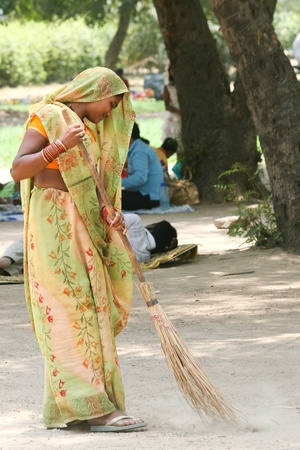 Young indian women in colorful traditional dresses sweeping in New Delhi, India on a Sunday morning. 27th June, 2010.