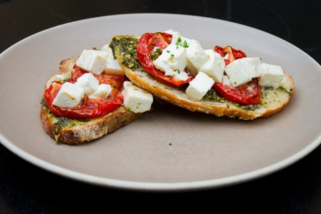 feta: Warm toasted bruschetta with topping of fresh and dry tomatoes, feta cheese and shredded basil leaves  Stock Photo