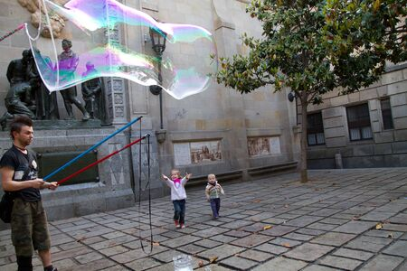 BARCELONA - MAY 14  Unknown street artist making giant soap bubbles and children playing with them on May 14, 2012 in Barcelona, Spain