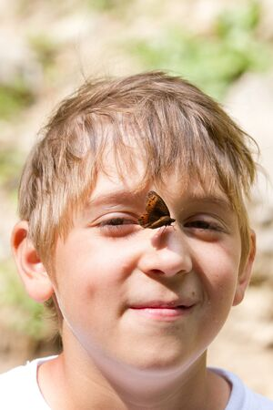 Outdoors summer shot of young boy smiling with butterfly on his nose photo