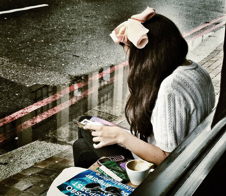 LONDON - AUGUST 22  Unidentified young lady having coffee in front of a coffee shop on a rainy day on August 22, 2012 in London, UK