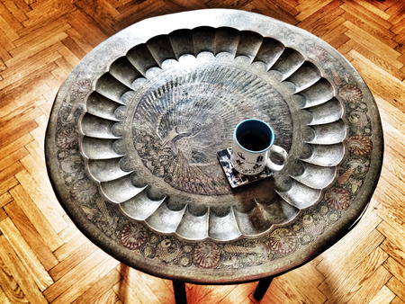 coffee mug on round oriental table over wooden floor photo