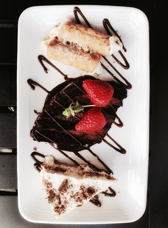 cannoli pastry: Italian deserts cake with tiramisu, chocolate cake with strawberries and mint topping and cannoli pastry with fistic