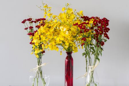 centres: Red chrysanthemum flowers with yellow centres in transparent glass vases of different shapes and yellow flowers in red vase over light grey background