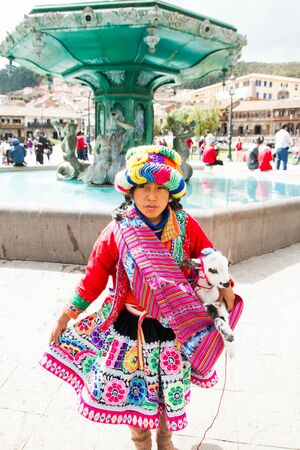 CUSCO - SEPTEMBER 02: Close-up of unknown local peruvian girl with lamb on background of tourists, locals and architectural details on the streets of Cusco, Peru on September 2nd, 2016.