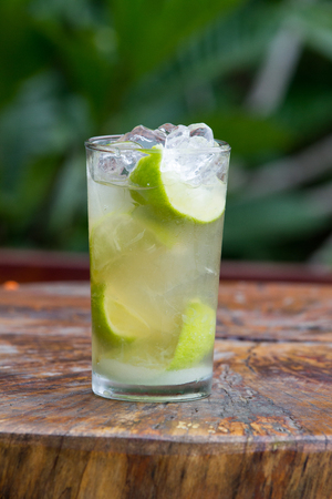 Glass of caipirinha on a wooden table outdoors