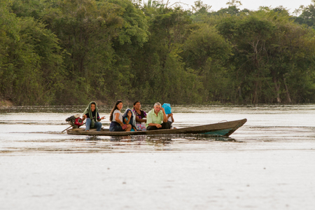 AMAZON, BRAZIL - DECEMBER 31: Unknown people on a boat in the rain on Rio Negro in the Amazon River basin, Brazil, South America on December 31st, 2017