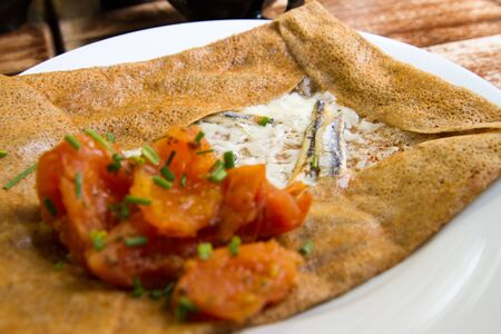 Savory crepe with cream cheese, anchovy and tomato