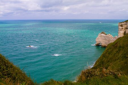 Etretat  chalk cliffs, including three natural arches and a pointed formation called LAiguille or the Needle.  Seine-Maritime department, Normandie, in north-western France. April 16th, 2017