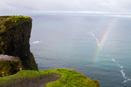 People in the distance watching a rainbow in the beautiful landscape at the famous Cliffs of Moher and  OBriens Tower in Co. Clare, Europe, ireland