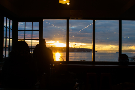 SEATTLE, WASHINGTON STATE -  JANUARY 2019 - Unknown people inside Pike Place Market watching from the sunset on Elliot Bay, Puget Sound in Seattle, Washington, USA in December 2018