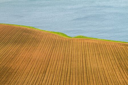 Scotland coast with half cultivated land and half water view