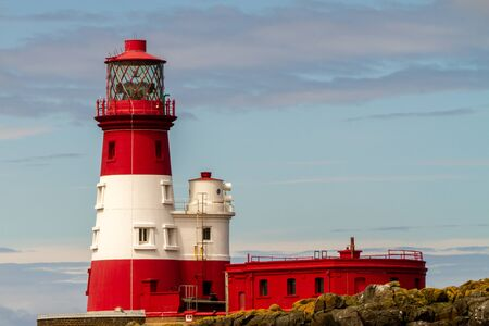 Longstone Lighthouse in white and red, on Longstone Rock in the outer group of the Farne Islands off the Northumberland Coast with seals in front