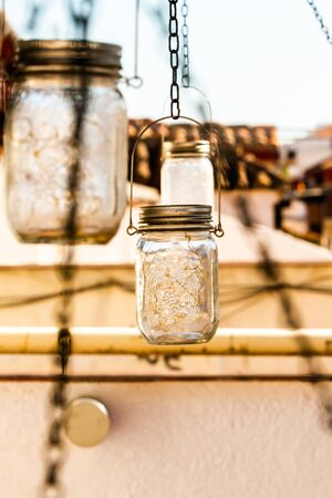 Solar powered mason jars providing light at night in urban garden Standard-Bild
