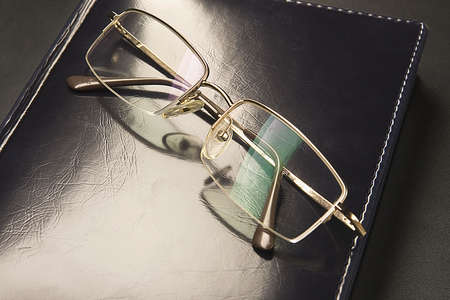 Glasses with gold-rimmed is lying on black leather an organizer photo