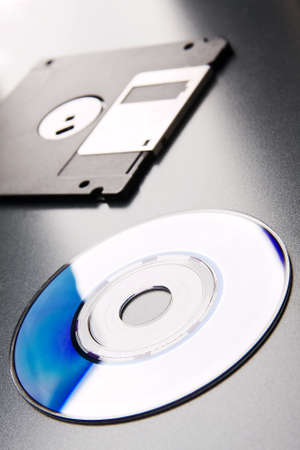 CD lays on a background floppy disk