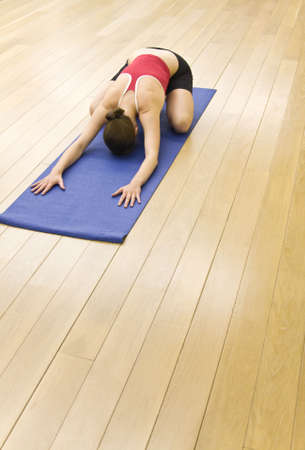 brune: The girl is engaged in yoga in a hall with a wooden floor Stock Photo