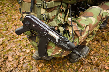 persuasion: The light machinegun hangs on a shoulder of the soldier dressed in a camouflage